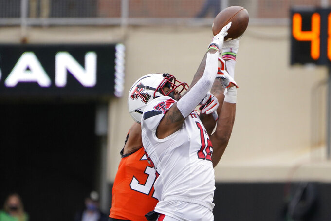 Oklahoma State safety Kolby Harvell-Peel, rear, breaks up a pass intended for Texas Tech wide receiver Ja'Lynn Polk (12) in the first half of an NCAA college football game in Stillwater, Okla., Saturday, Nov. 28, 2020. (AP Photo/Sue Ogrocki)