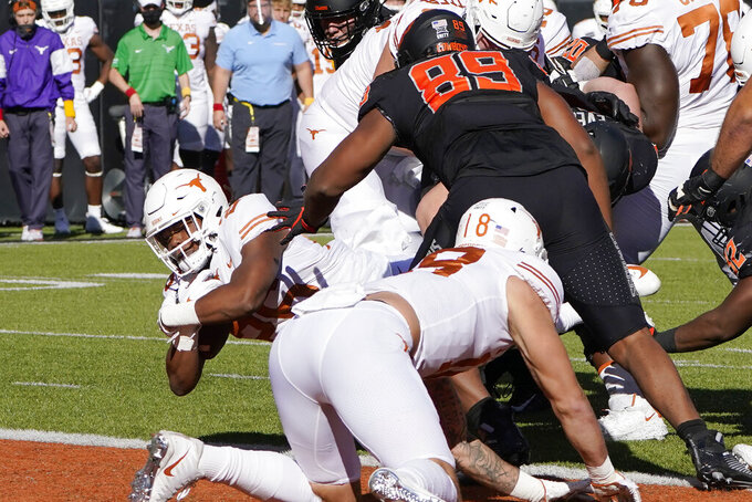 Texas running back Keaontay Ingram, left, dives into the end zone for a touchdown in front of Oklahoma State defensive end Tyler Lacy (89) in the first half of an NCAA college football game in Stillwater, Okla., Saturday, Oct. 31, 2020. (AP Photo/Sue Ogrocki)
