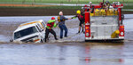Phillip Schultz, center, of Junction City, Ore. is rescued from his truck by Junction City Rural Fire and Lane County Sheriff Deputies after he became stuck in flood water on Noraton Lane just off Highway 99 East north of Junction City, Ore. Tuesday April 9, 2019. (Chris Pietsch/The Register-Guard via AP)