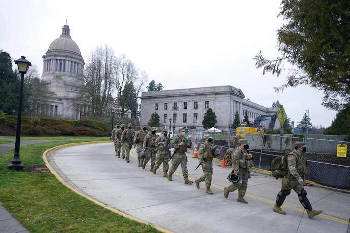 Washington National Guard members walk in formation away from the Legislative Building, Wednesday, Jan. 20, 2021, at the Capitol in Olympia, Wash. Members of the Guard and Washington State Patrol troopers have been in place all week on the campus providing security against possible protests connected with the inauguration of President Joe Biden and the departure of former President Donald Trump in Washington, D.C. (AP Photo/Ted S. Warren)