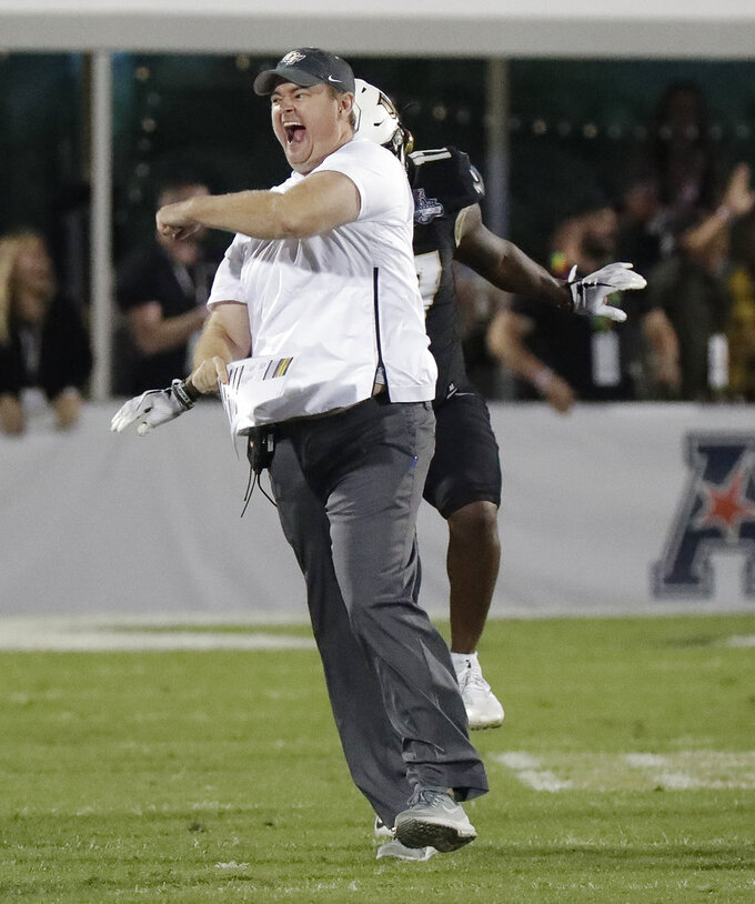 Central Florida head coach Josh Heupel runs on the field and celebrates during the final seconds of the American Athletic Conference championship NCAA college football game against Memphis, Saturday, Dec. 1, 2018, in Orlando, Fla. (AP Photo/John Raoux)