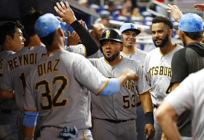 Pittsburgh Pirates' Melky Cabrera (53) is congratulated by teammates after he scored on a double by Josh Bell during the seventh inning of a baseball game against the Miami Marlins, Sunday, June 16, 2019, in Miami. (AP Photo/Wilfredo Lee)