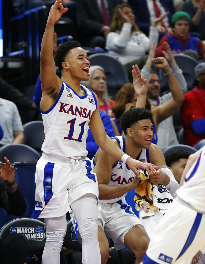 Kansas guard Devon Dotson (11) reacts after a teammate scores a three-point basket against Northeastern in the second half during a first round men's college basketball game in the NCAA Tournament, Thursday, March 21, 2019, in Salt Lake City. (AP Photo/Rick Bowmer)