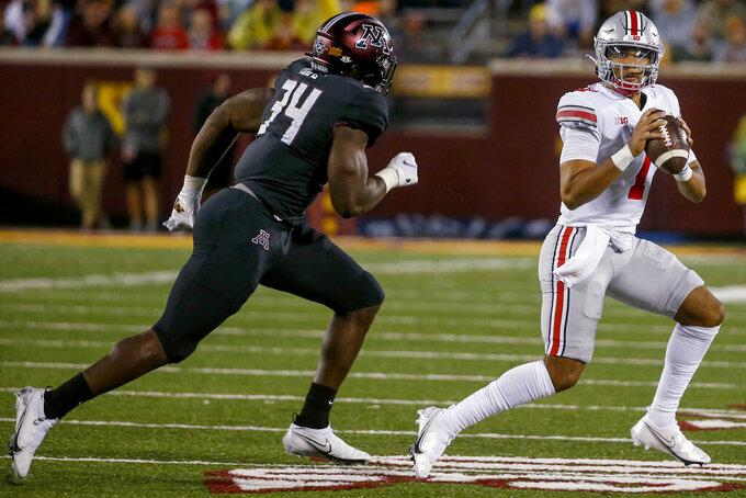 Ohio State quarterback C.J. Stroud (7) eludes the pressure of Minnesota defensive lineman Boye Mafe (34) during the second quarter of an NCAA college football game Thursday, Sept. 2, 2021, in Minneapolis. Ohio State won 45-31. (AP Photo/Bruce Kluckhohn)