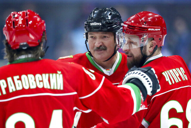 FILE In this file photo taken on Saturday, March 28, 2020, Belarusian President Alexander Lukashenko, centre, takes part in a hockey match during Republican amateur competitions in Minsk, Belarus. Amid concern about the coronavirus pandemic, Belarus' president made a public appearance in protective gear much different from the face masks and hazmat suits seen around the world. Alexander Lukashenko was clad in a helmet and knee guards for a hockey game at a rink full of spectators. The new coronavirus causes mild or moderate symptoms for most people, but for some, especially older adults and people with existing health problems, it can cause more severe illness or death. (Andrei Pokumeiko/BelTA Pool Photo via AP, File)