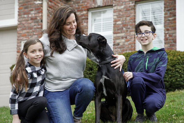 In this March 27, 2020 photo, Kim Simeon and children Annabel, 9, and Brennan, 11, pose for a photo with Nala, a dog they are fostering, in Omaha, Neb. The Simeon family was headed home to Omaha from a much-needed Smoky Mountains vacation when Kim Simeon spotted a social media post from the Nebraska Humane Society, pleading with people to consider fostering a pet.   (AP Photo/Nati Harnik)