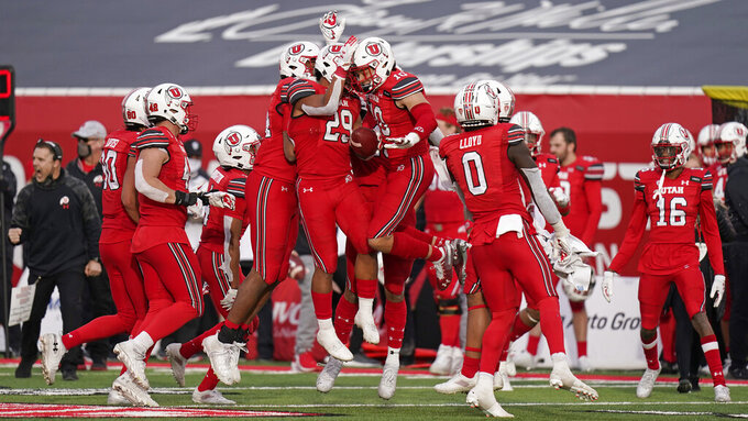 Utah players celebrate their fumble recovery against Washington State during the second half of an NCAA college football game Saturday, Dec. 19, 2020, in Salt Lake City. (AP Photo/Rick Bowmer)