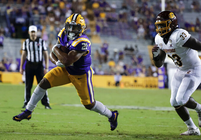 LSU running back Corey Kiner (21) runs past Central Michigan linebacker Kumehnnu Gwilly (33) for a touchdown during the fourth quarter of an NCAA college football game in Baton Rouge, La,. Saturday, Sept. 18, 2021. (AP Photo/Derick Hingle)