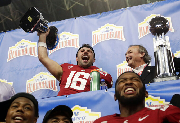 Washington State quarterback Gardner Minshew (16) holds his Offensive Player of the Game trophy as he celebrates the team's 28-26 win over Iowa State in the Alamo Bowl NCAA college football game, Friday, Dec. 28, 2018, in San Antonio. (AP Photo/Eric Gay)