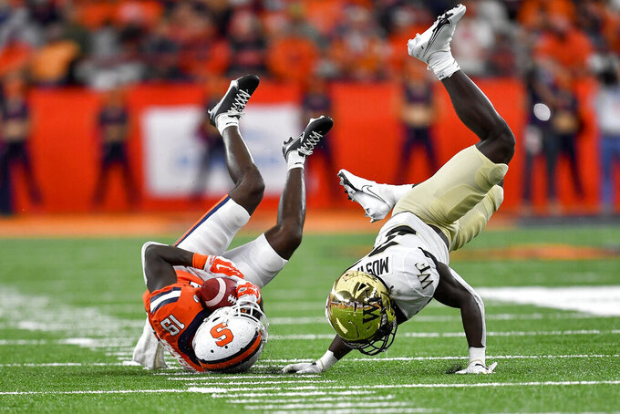 Syracuse wide receiver Sharod Johnson (19) is tackled by Wake Forest defensive back Malik Mustapha (27) during the first half of an NCAA college football game in Syracuse, N.Y., Saturday, Oct. 9, 2021. (AP Photo/Adrian Kraus)