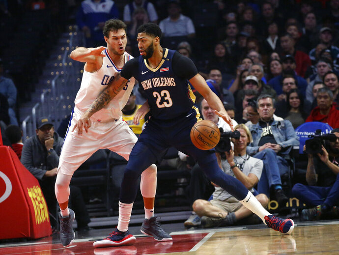 FILE- In this Jan. 14, 2019, file photo New Orleans Pelicans' Anthony Davis, right, dribbles against Los Angeles Clippers' Danilo Gallinari during the first half of an NBA basketball game in Los Angeles. Davis' agent says the five-time All-Star has told the New Orleans Pelicans that he wants to be traded to a contending team. Agent Rich Paul confirmed the request to The Associated Press early Monday, Jan. 28. (AP Photo/Ringo H.W. Chiu, File)