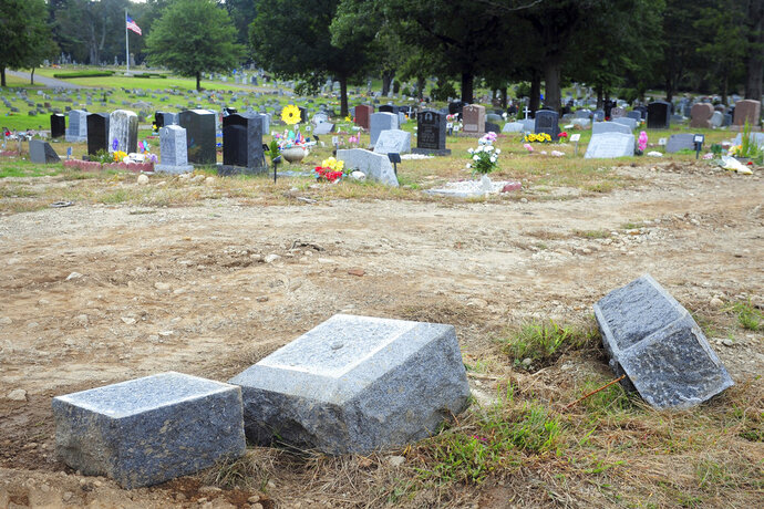 FILE - In this Oct. 2, 2018 file photo, toppled headstones rest on the ground in Park Cemetery in Bridgeport, Conn. A mass desecration of graves at the Connecticut cemetery has devastated dozens of families while police determine whether to file criminal charges. Authorities say gravestones and human remains at the cemetery were moved to make way for the newly dead. (Ned Gerard/Hearst Connecticut Media via AP, File)