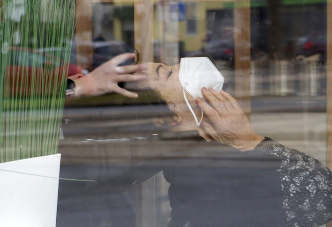 A woman with a mask is at a hairdresser after lock down in Vienna, Austria, Monday, Feb. 8, 2021. Photographed through a pane of glass. The Austrian government has moved to restrict freedom of movement for people, in an effort to slow the onset of the COVID-19 coronavirus. (AP Photo/Ronald Zak)