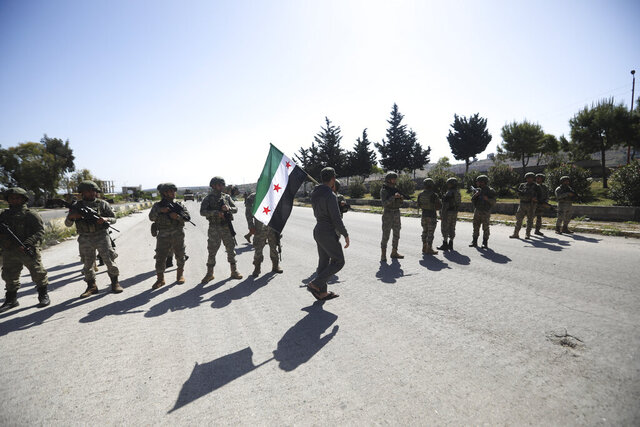 A man carries Syrian Independence flag as Turkish soldiers block a road after a nearby explosion outside the city of Ariha, in Idlib province, Syria, Tuesday, May 12, 2020. (AP Photo/Ghaith Alsayed)