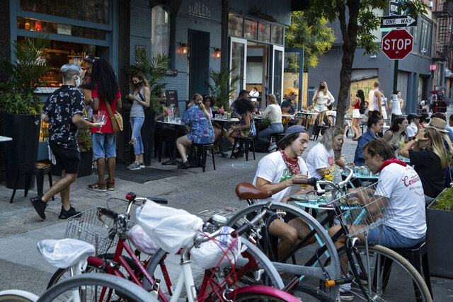 Customers dine outside Dudley's, Monday, June 22, 2020, in New York. New York City Mayor Bill de Blasio says he is delaying the planned resumption of indoor dining at restaurants in the city out of fear it would ignite a a spike in coronavirus infections. (AP Photo/John Minchillo)