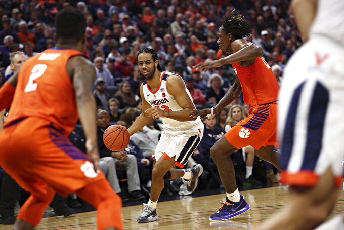 Virginia guard Tomas Woldetensae (53) dribbles the ball between Clemson defenders during an NCAA college basketball game Wednesday, Feb. 5, 2020, in Charlottesville, Va. (Erin Edgerton/The Daily Progress via AP)