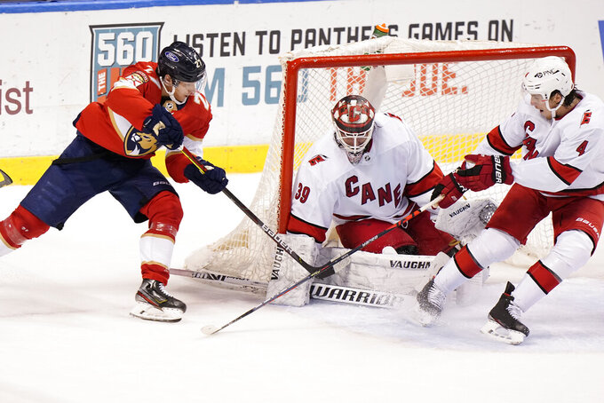 Florida Panthers center Eetu Luostarinen (27) takes a shot against Carolina Hurricanes goaltender Alex Nedeljkovic (39) and defenseman Haydn Fleury (4) during the third period of an NHL hockey game, Monday, March 1, 2021, in Sunrise, Fla. (AP Photo/Wilfredo Lee)