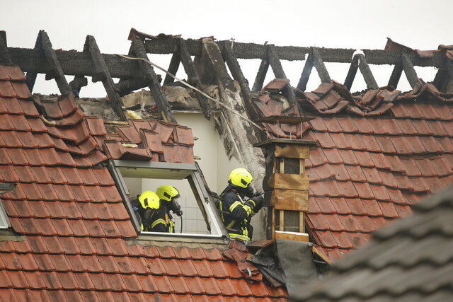Emergency services attend the scene after a light plane crashed into an apartment building in Wesel, Germany, Saturday July 25, 2020. Three people died on Saturday after an ultra-light aircraft crashed into the apartment building and caught fire.(David Young/dpa via AP)