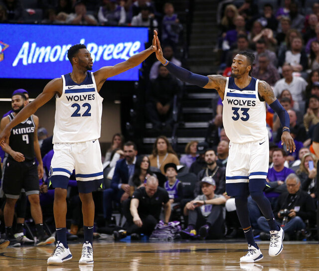 Minnesota Timberwolves' Andrew Wiggins, left, and Robert Covington high-five during a timeout in the closing moments of the their second overtime against the Sacramento Kings in an NBA basketball game in Sacramento, Calif., Thursday, Dec. 26, 2019. The Timberwolves won in double-overtime 105-104. (AP Photo/Rich Pedroncelli)