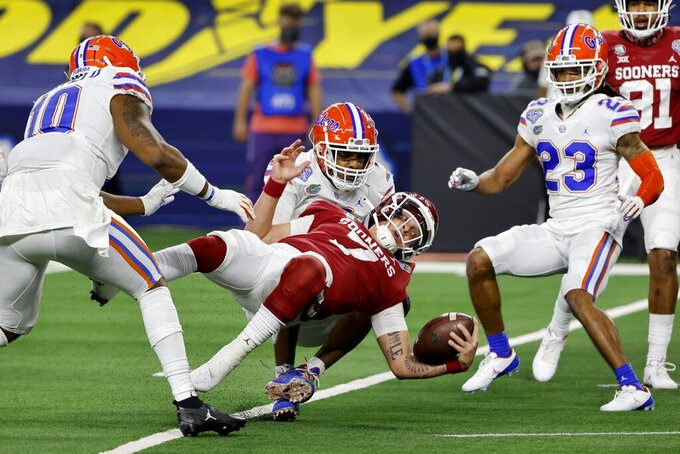 Oklahoma quarterback Spencer Rattler (7) is pulled down from behind by Florida linebacker Mohamoud Diabate, center rear, but not before scoring a touchdown, as linebacker Andrew Chatfield Jr. (10) and defensive back Jaydon Hill (23) watch during the first half of the Cotton Bowl NCAA college football game in Arlington, Texas, Wednesday, Dec. 30, 2020. (AP Photo/Michael Ainsworth)