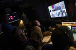 In this Monday, Jan. 13, 2020 photo, Dakar TV staffers work inside the broadcast truck after stage eight in Wadi Al Dawasir, Saudi Arabia. Formerly known as the Paris-Dakar Rally, the race was created by Thierry Sabine after he got lost in the Libyan desert in 1977. Until 2008, the rallies raced across Africa, but threats in Mauritania led organizers to cancel that year's event and move it to South America. It has now shifted to Saudi Arabia. The race started on Jan. 5 with 560 drivers and co-drivers, some on motorbikes, others in cars or in trucks. Only 41 are taking part in the Original category. (AP Photo/Bernat Armangue)