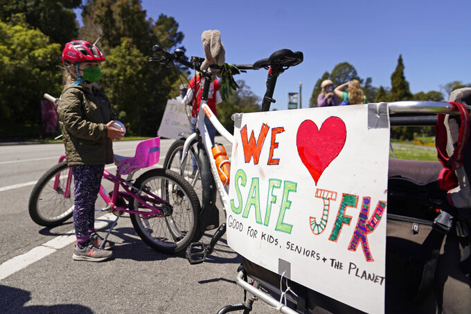 Luna Darr, 5, stands by her bike along with her father's during a celebration to mark the one-year anniversary of car-free John F. Kennedy Drive in Golden Gate Park, Wednesday, April 28, 2021, in San Francisco. At the start of the pandemic, San Francisco closed off parts of a major beachfront highway and Golden Gate Park to cars so that people had a safe place to run and ride bikes. Open space advocates want to keep those areas car-free as part of a bold reimagining of how U.S. cities look. But opponents decry the continued closures as elitist, unsafe and nonsensical now that the pandemic is over and people need to drive again. (AP Photo/Eric Risberg)