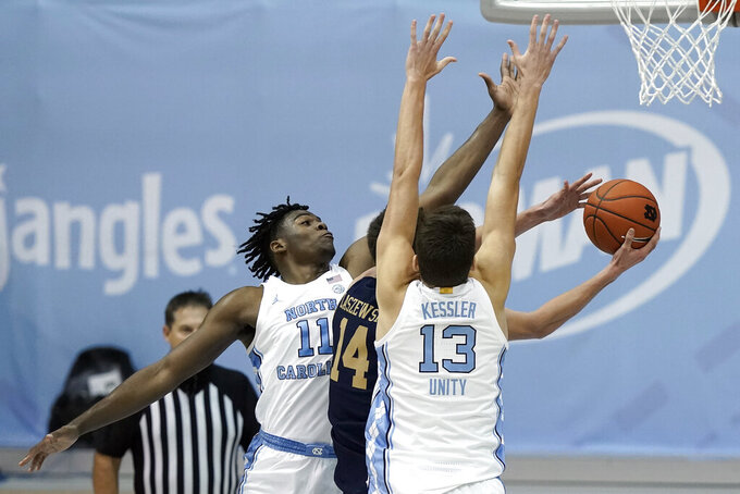 North Carolina forwards Day'Ron Sharpe (11) and Walker Kessler (13) guard against Notre Dame forward Nate Laszewski (14) during the first half of an NCAA college basketball game in Chapel Hill, N.C., Saturday, Jan. 2, 2021. (AP Photo/Gerry Broome)