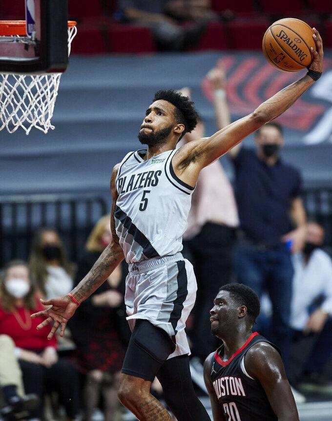 Portland Trail Blazers forward Derrick Jones Jr. dunks over Houston Rockets forward Khyri Thomas during the second half of an NBA basketball game in Portland, Ore., Monday, May 10, 2021. (AP Photo/Craig Mitchelldyer)