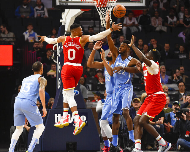 Houston Rockets guard Russell Westbrook (0) passes behind his back to center Clint Capela, right, as Minnesota Timberwolves center Karl-Anthony Towns (32), forward Andrew Wiggins (22) and guard Shabazz Napier (13) look on during the first half of an NBA basketball game Friday, Jan. 24, 2020, in Minneapolis. (AP Photo/Craig Lassig)