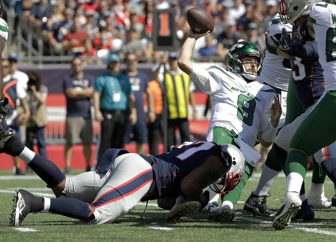 New York Jets quarterback Luke Falk (8) tries to pass while he is dragged down by New England Patriots defensive end Michael Bennett, left, in the first half of an NFL football game, Sunday, Sept. 22, 2019, in Foxborough, Mass. (AP Photo/Steven Senne)