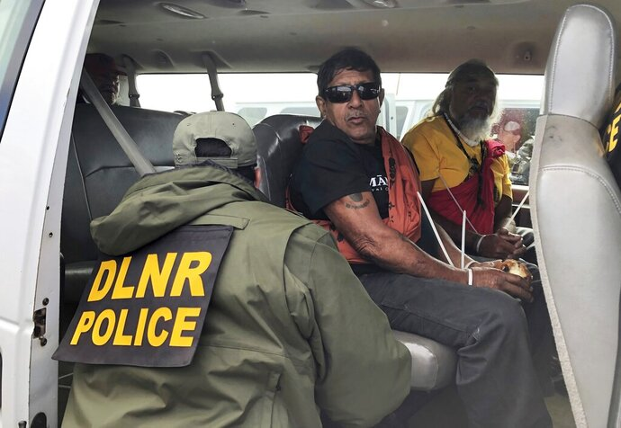File - In this July 17, 2019, file photo, officers from the Hawaii Department of Land and Natural Resources arrest protesters, many of them elderly, who are blocking a road to prevent construction of a giant telescope on a mountain that some Native Hawaiians consider sacred, on Mauna Kea on the Big Island of Hawaii. To avoid the appearance of a conflict of interest, the Hawaii attorney general's office will take over prosecution of protesters arrested for blocking construction of the giant telescope. Big Island prosecutor Mitch Roth said Wednesday, Sept. 18, 2019, he turned over the cases in response to an Associated Press story highlighting concerns that his son's employment with a telescope partner is a possible conflict. (Cindy Ellen Russell/Honolulu Star-Advertiser via AP, File)