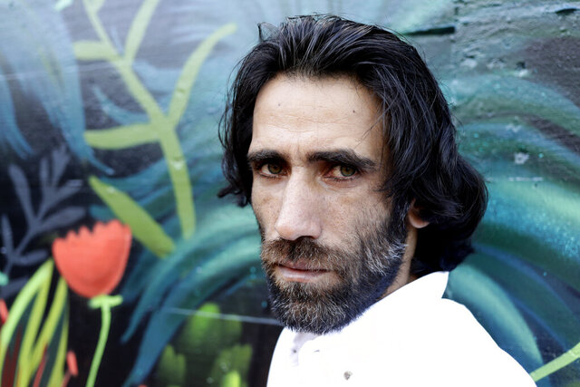 FILE - In this Nov. 19, 2019, file photo, Behrouz Boochani, the Kurdish film-maker, writer and refugee who has documented life inside the Australian offshore immigration camp on Manus Island, poses for a portrait in Christchurch, New Zealand.  The refugee who wrote an award-winning book while being held in detention has overstayed his visa in New Zealand, according to at least one official and the man's lawyer, in a move that could fuel diplomatic tensions with Australia. (AP Photo/Mark Baker, File)