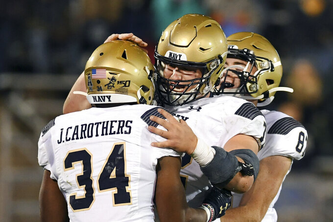 Navy fullback Jamale Carothers (34) is congratulated by his teammates during the second half of an NCAA college football game against Connecticut on Friday, Nov. 1, 2019, in East Hartford, Conn. (AP Photo/Stephen Dunn)