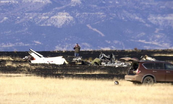 FILE - In this Jan. 19, 2018, file image taken from video, an investigator photographs the where a helicopter crashed near Raton, N.M. A report released this week says investigators found no problems with a helicopter that crashed in New Mexico in January 2018, killing five people including Zimbabwe opposition leader Roy Bennett. The National Transportation Safety Board said the pilot apparently caused the fatal wreck by flying too low over mountainous terrain at night. (AP Photo/Peter Banda, file)