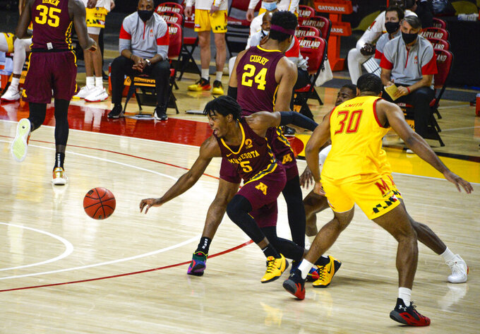 Minnesota's Marcus Carr, front left, splits the defense against Maryland during the first half of an NCAA college basketball game, Sunday, Feb. 14, 2021, in College Park, Md. (Kevin Richardson/The Baltimore Sun via AP)