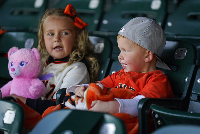 Braxton Moore, 4, and his sister Madison, 6, of Sacramento, Calif., watch batting practice before the start of an opening day baseball game between the San Francisco Giants and the Colorado Rockies, Friday, April 9, 2021, in San Francisco. (AP Photo/Eric Risberg)