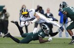 Michigan quarterback Shea Patterson (2) is upended by Michigan State safety David Dowell (6) during the first half of an NCAA college football game, Saturday, Oct. 20, 2018, in East Lansing, Mich. (AP Photo/Carlos Osorio)