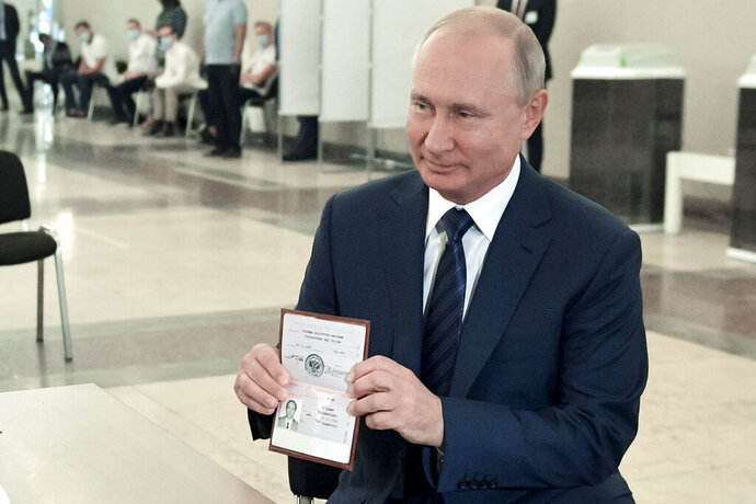 Russian President Vladimir Putin shows his passport to a member of an election commission as he arrives to take part in voting at a polling station in Moscow, Russia, Wednesday, July 1, 2020. The vote on the constitutional amendments that would reset the clock on Russian President Vladimir Putin's tenure and enable him to serve two more six-year terms is set to wrap up Wednesday. (Alexei Druzhinin, Sputnik, Kremlin Pool Photo via AP)