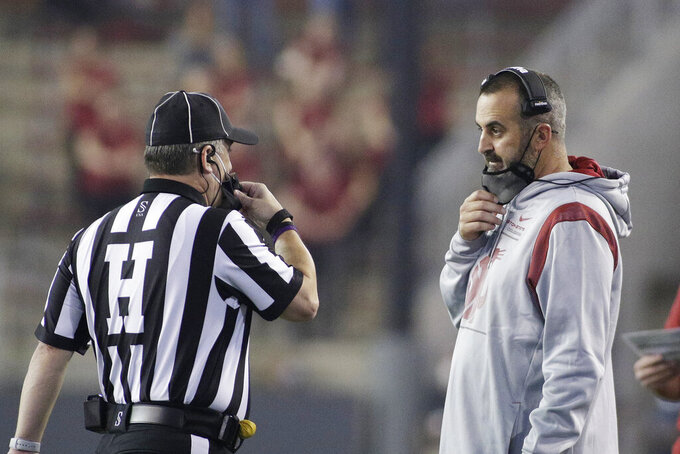 Washington State head coach Nick Rolovich, right, speaks with an official during the second half of an NCAA college football game, Saturday, Sept. 4, 2021 against Utah State, in Pullman, Wash. Utah State won 26-23. (AP Photo/Young Kwak)