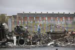 "FILE - In this Thursday, April 8, 2021 file photo, a man walks past a burnt out bus on the Shankill road in West Belfast, Northern Ireland. The chaotic scenes during a week of violence on the streets of Northern Ireland have stirred memories of decades of Catholic-Protestant conflict, known as ""The Troubles."" A 1998 peace deal ended large-scale violence but did not resolve Northern Ireland's deep-rooted tensions. (AP Photo/Peter Morrison, File)"