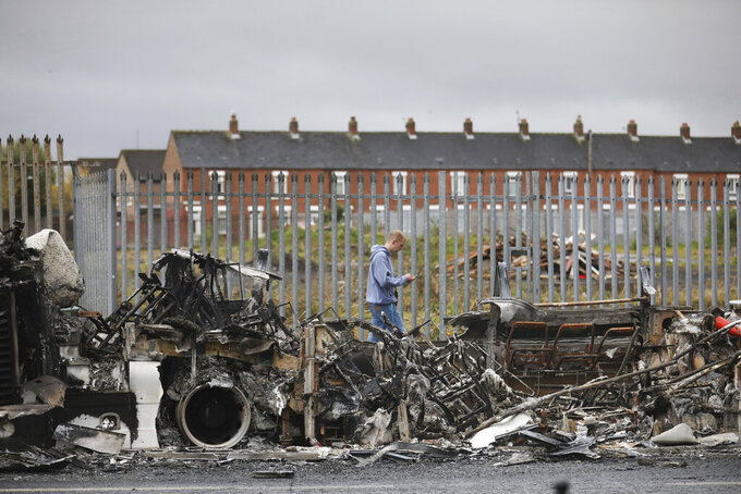 A man walks past a burnt out bus on the Shankill road in West Belfast, Northern Ireland, Thursday, April 8, 2021. The scene follows another night of violence in Loyalist areas that has now spread to interface areas of the peace divide. (AP Photo/Peter Morrison)