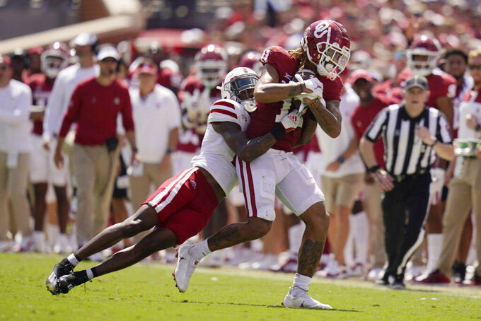 Oklahoma wide receiver Jadon Haselwood (11) is tackled by Nebraska cornerback Quinton Newsome, left, in the second half of an NCAA college football game, Saturday, Sept. 18, 2021, in Norman, Okla. (AP Photo/Sue Ogrocki)