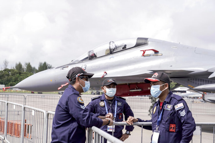 The Royal Malaysian Air Force personnel wear masks at the Static Aircraft Display area at the Singapore Airshow in Singapore Tuesday, Feb. 11, 2020 in Singapore. Singapore's air show began Tuesday with the usual ribbon cutting, but less typical warnings to industry and military figures attending to avoid handshakes and other close contact to avoid spreading a virus that has sickened tens of thousands of people. (AP Photo/Danial Hakim)
