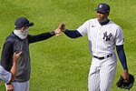 New York Yankees manager Aaron Boone, left, congratulates relief pitcher Aroldis Chapman after Chapman earned the save in the Yankees victory over the Baltimore Orioles in a baseball game, Sunday, Sept. 13, 2020, at Yankee Stadium in New York. (AP Photo/Kathy Willens)