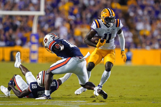 LSU wide receiver Brian Thomas Jr. (11) carries against Auburn cornerback Nehemiah Pritchett (18) and safety Zion Puckett (10) during the first half of an NCAA college football game in Baton Rouge, La., Saturday, Oct. 2, 2021. (AP Photo/Gerald Herbert)