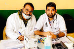 In this October 2019 photo provided by Bharat Sangwan, Joginder Chaudhary, left, and his friend and colleague Sangwan volunteer at a medical camp for women. After the virus killed the 27-year-old Chaudhary in late July 2020, his mother wept inconsolably. With her son gone, Premlata Chaudhary said, how could she go on living? Three weeks later, on Aug. 18, the virus took her life, too — yet another number in an unrelenting march toward a woeful milestone.(Courtesy of Bharat Sangwan via AP)