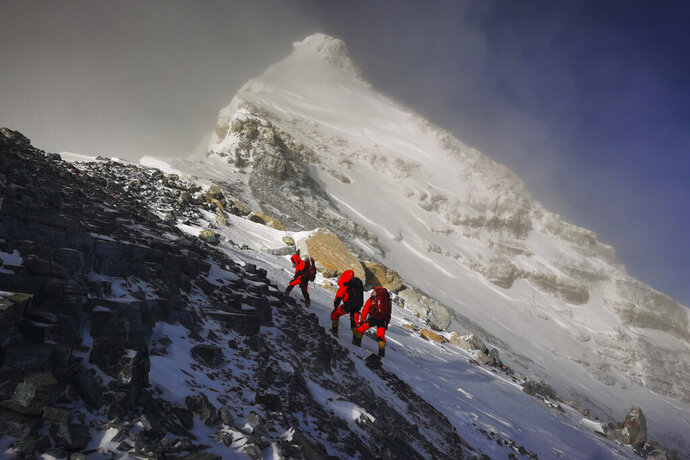 In this photo released by Xinhua News Agency, members of a Chinese surveying team head for the summit of Mount Everest, also known locally as Mt. Qomolangma, Wednesday, May 27, 2020. The Chinese government-backed team plans to summit Mount Everest this week at a time when the world's tallest peak has been closed to commercial climbers. (Tashi Tsering/Xinhua via AP)