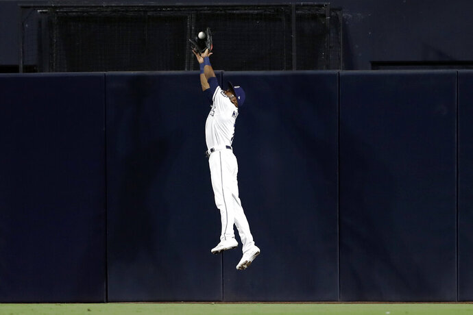 San Diego Padres center fielder Manuel Margot makes the catch above the wall for the out on Chicago Cubs' Nicholas Castellanos during the fourth inning of a baseball game Wednesday, Sept. 11, 2019, in San Diego. (AP Photo/Gregory Bull)