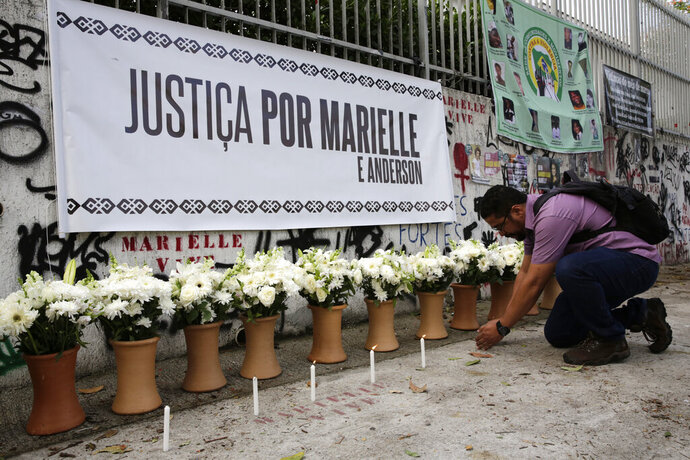 "A man lights a candle in front of a row of vases filled with flowers and a poster with a message that reads in Portuguese: ""Justice for Marielle and Anderson,"" at the site where Rio councilwoman Marielle Franco was gunned down, during a demonstration marking the one year anniversary of her death, in Rio de Janeiro, Brazil, Thursday, March 14, 2019.  Authorities arrested two former police officers Tuesday in the killing of Franco and her driver Anderson Gomes, a brazen assassination that shocked Brazilians and sparked protests in several countries. (AP Photo/ Silvia Izquierdo)"