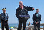 New Jersey Gov. Phil Murphy, center, speaks at a news conference at Island Beach State Park in New Jersey on Wednesday, May 19, 2021, where he announced that the state will give free season-long admission to the park and other state parks to any New Jersey resident who has gotten at least one dose of COVID-19 vaccine by July 4. Other incentives to get people to take the shot include a free glass of wine at participating wineries. (AP Photo/Wayne Parry)